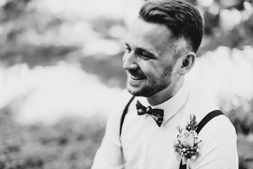 Portrait of a beautiful groom in a white shirt with suspenders who smiles. Black and white photo