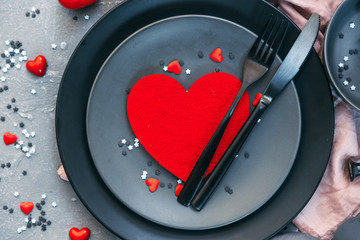 Romantic dinner concept. Valentine day or proposal background. Top view of restaurant wooden table with heart and rose with cutlery on plate