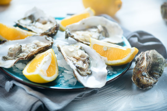 Fresh oysters close-up on blue plate, served table with oysters, lemon in restaurant. Gourmet food