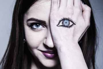 Staring brunette woman with painted eyes  on her hand as a symbol of not fair play and double standards (gestures, body language, psychology concept)