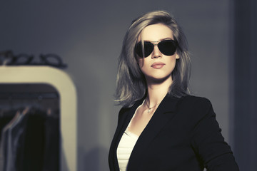Young fashion blond woman in sunglasses in the mall interior