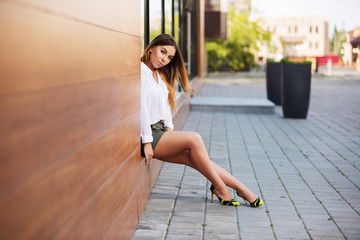Young fashion woman in white blouse and short skirt at the mall window