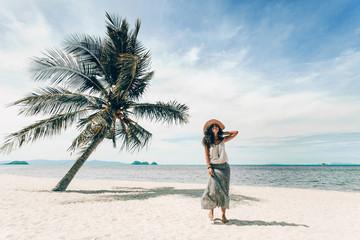 cheerful young woman having fun on tropical island beach