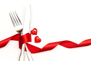Valentine's day meal concept. knife and fork with red ribbon and love hearts