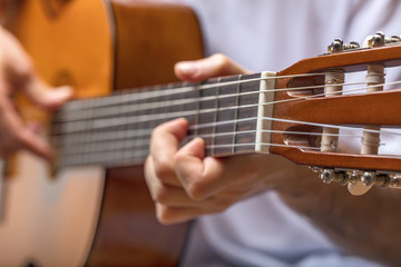 Young man's hand tuning acoustic guitar.