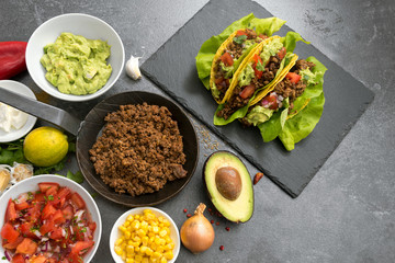 stuffed mexican tacos and ingredients like fried ground beef, tomato salsa, guacamole, corn and spices on a dark slate plate, top view from above