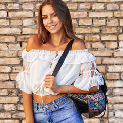 Lifestyle street portrait of beautiful girl with bag