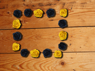 A photo frame with handmade roses on wooden background. Romantic background.