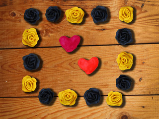 A photo frame with handmade flowers and heart on wooden background. Romantic background.
