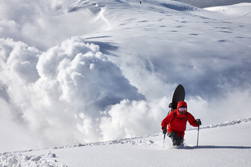 Snowboarder hiking on snow during winter
