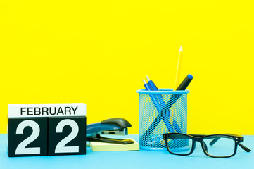 February 22nd. Day 22 of february month, calendar on yellow background with office supplies. Winter time