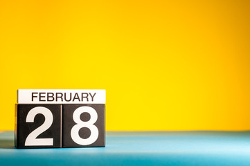 February 28th. Day 28 of february month, calendar on yellow background. Winter time, leap-year. Empty space for text