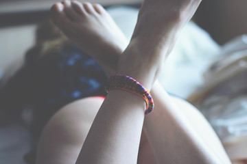 Girl with colorful bracelets on the leg lying on a white bed.