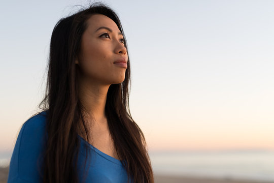 Young Asian woman looking at sunset sky
