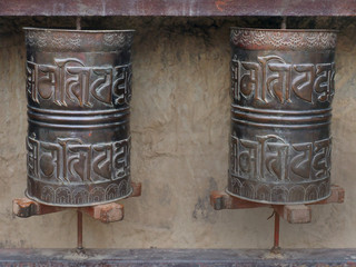 Two Buddhist prayer drums with mantras in Sanskrit in a niche of stone wall are a Tibetan monastery.