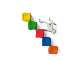 Plasticine clay made blocks stacked staircase,person falling down the stairs,on white background.It's like a most successful business,but make some mistakes can cause serious damage.So be very careful