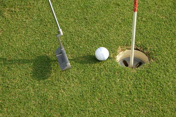 A short put in the game of golf with a ball and a putter