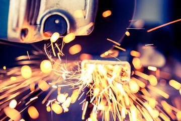 Soft focus with sparks flying from metal being bar cut with electric grinder