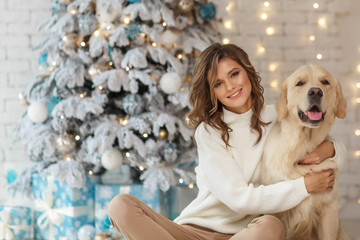 Beautiful young woman with a golden retriver dog near christmas tree