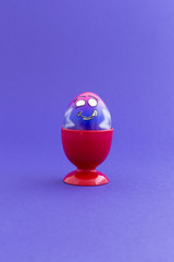 Pink and purple painted Easter egg with funny cartoon style face in a red plastic egg cup and purple background