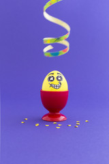 Yellow painted Easter egg with funny cartoon style face in a red plastic egg cup, colorful paper streamer and confetti on purple background