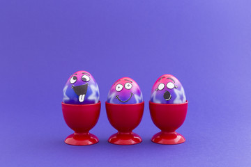 Group of colorful painted Easter eggs with funny cartoon style faces in red plastic egg cups on purple background
