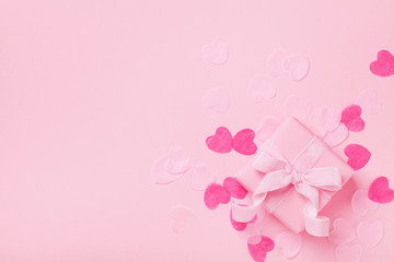 Fashion background with gift or present box and paper hearts. Pink pastel color. Greeting card for Valentines, Woman or Mothers Day. Flat lay.