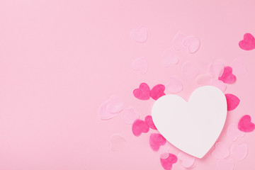 White wooden heart and paper hearts on pink pastel background top view. Greeting card for Valentines, Woman or Mothers Day. Wedding mockup. Flat lay.