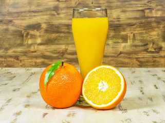 A glass of fresh orange juice and oranges on wooden background