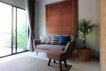 interior design for living area in modern style with plant, curtain, brick wall, wood curtain window design and Bamboo rug