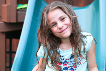 Close-up Portrait of Cute Beautiful Five Years Old Girl Looks at Camera Smiling at the Playground, at Warm Summer Day in Portland Oregon USA