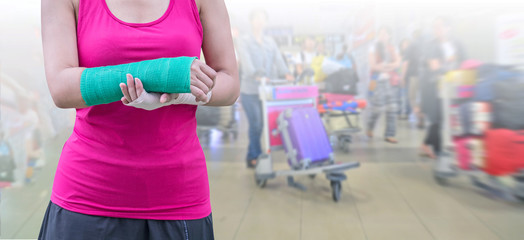 woman with accident on arm isolated on blurred background traveler with suitcase in airport, clipping path included, insurance travel concept