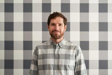 Smiling young man wearing a checkered shirt matching his wallpaper