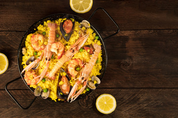 Spanish seafood paella in paellera, with lemons and copyspace