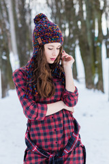 In winter, the girl poses in a colored cap, a checked shirt.