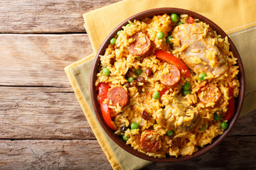 Arroz Valenciana with rice, meat, sausage, raisins, vegetables and spices close up in a bowl. horizontal top view