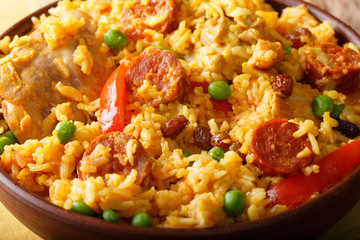 Arroz Valenciana with rabbit, chorizo, vegetables and spices macro in a bowl. horizontal