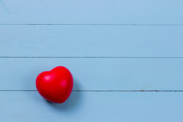 Red heart on wooden background color blue with copy space.