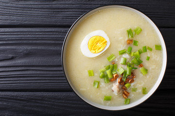 Arroz Caldo soup with rice, chicken and egg close-up. horizontal top view
