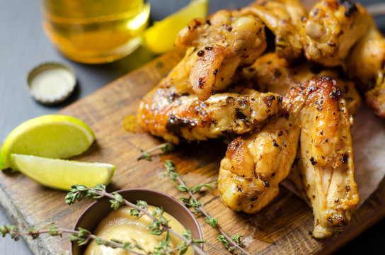 Roasted chicken wings with mustard and lime, beer on background.