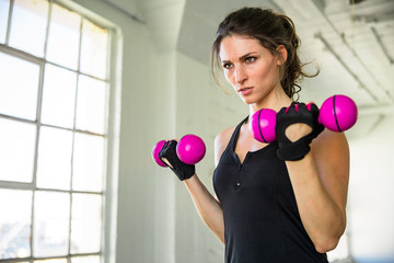 Intense inspirational motivated female athlete exercising toned arms in industrial gym