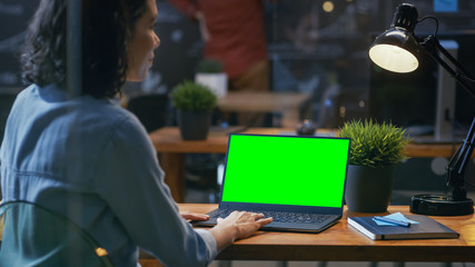 Female Office Worker at Her Desk Works on a Laptop with Mock-up Green Screen. Over the Shoulder Footage. She sits at the Wooden Desk in Creative Office.