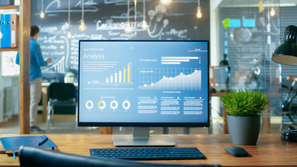 Personal Computer with Mobile Application Design Showing on the Monitor Stands on the Office Desk, In the Background Man Working in the Daytime Office Environment. Wall mural