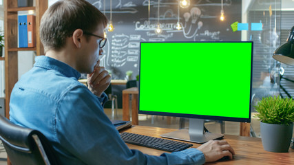 Young Man Works at His Desk on the Personal Computer with Mock-up Green Screen. In the Background His Colleague Works in the Creative Office. Wall mural