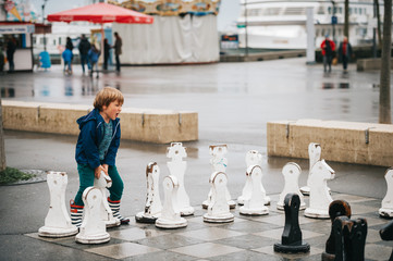 Kid boy playing giant chess on playground, wearing rain coat and boots. Image taken in Ouchy, Lausanne, Switzerland