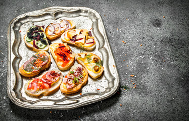 Various sandwiches with red caviar, bacon, cheese and fresh vegetables on a steel tray.