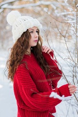 On a winter sunny day, a young girl with long hair poses in a white hat and a red sweater.