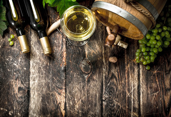 Wine background. A barrel of white wine with branches of green grapes.
