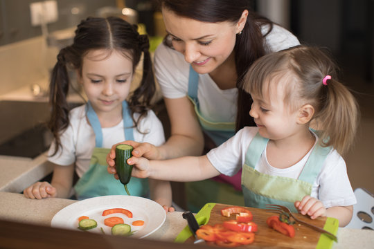 Happy family in the kitchen. Mom and daughters playing and having fun in the kitchen preparing.