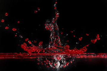 Red polystyrene  spherules splashing in water